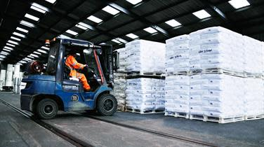 A forklift loading pallets of goods inside a DFDS warehouse
