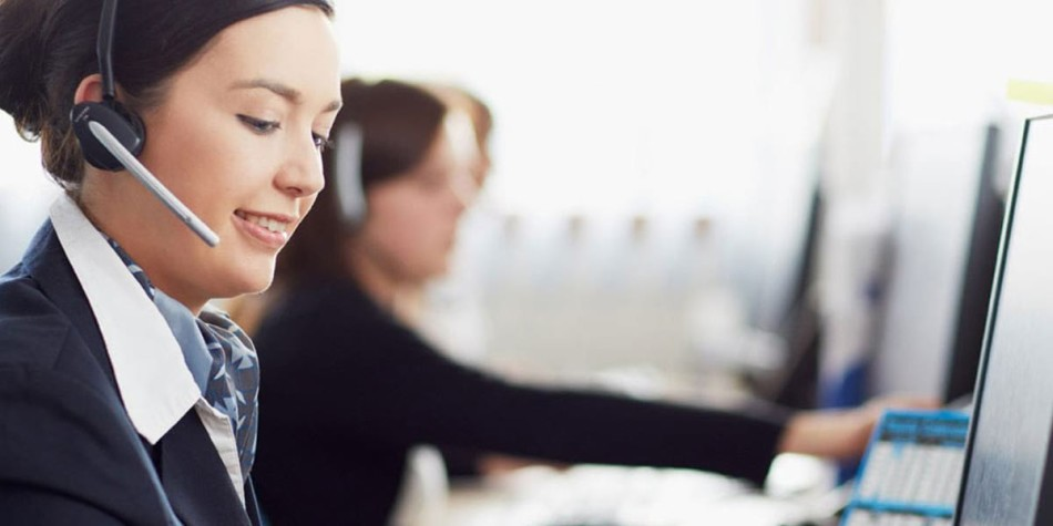A woman listening to a customer on a headset in the customer service office