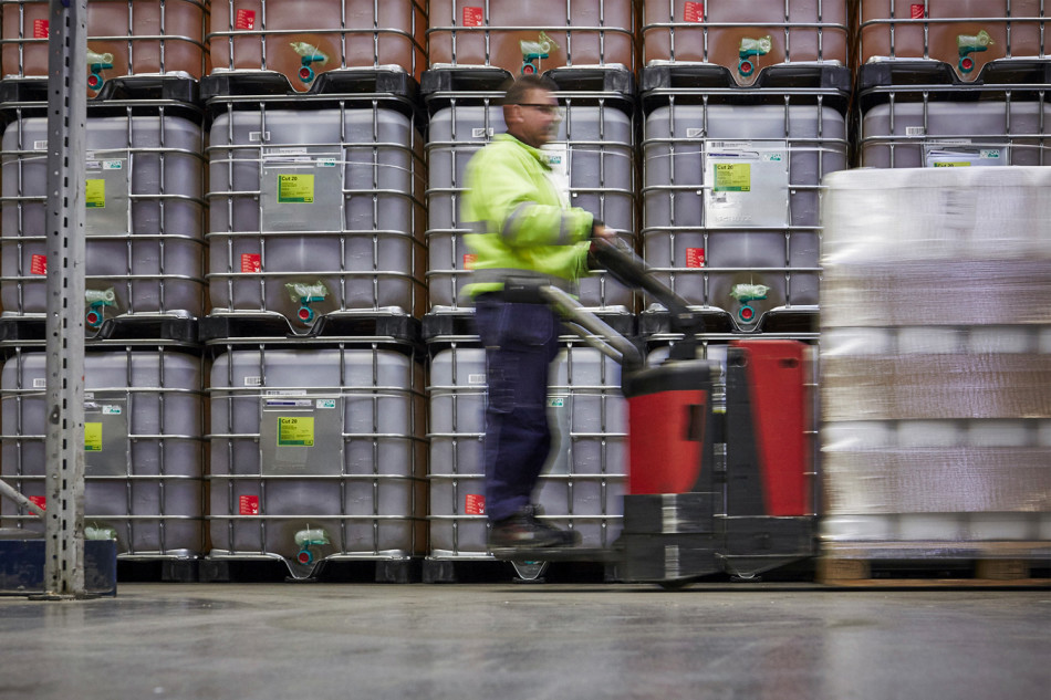 A DFDS Logistics employee moving chemicals inside a warehouse