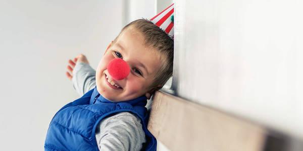 Gutt på med sirkushatt på dekk