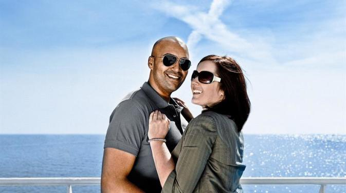 A couple on the top deck of a DFDS passenger ferry on a sunny day