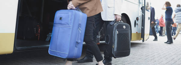 Loading luggage onto bus transfer