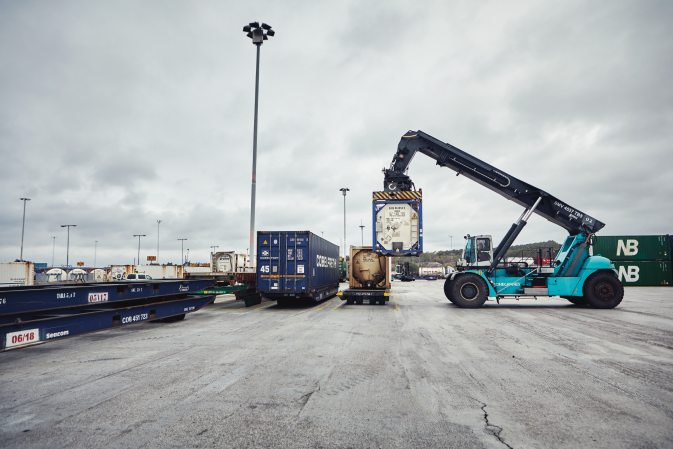 A DFDS Logistics reach stacker lifting a tank at a terminal