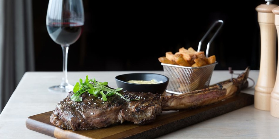 A portion of steak and chips on a wooden board with a glass of red wine on the side.