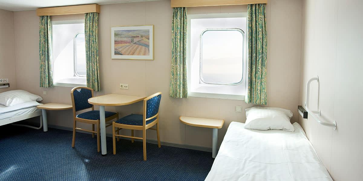 Bett, Tisch und zwei Stühle in Barrierefreie Kabine