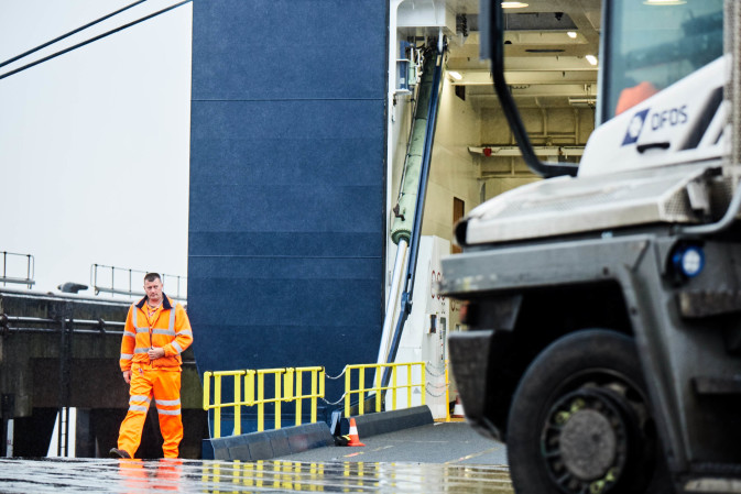 Employee walking past a DFDS vessel and truck