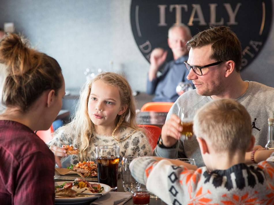 A family dining at our onboard restaurant Little Italy