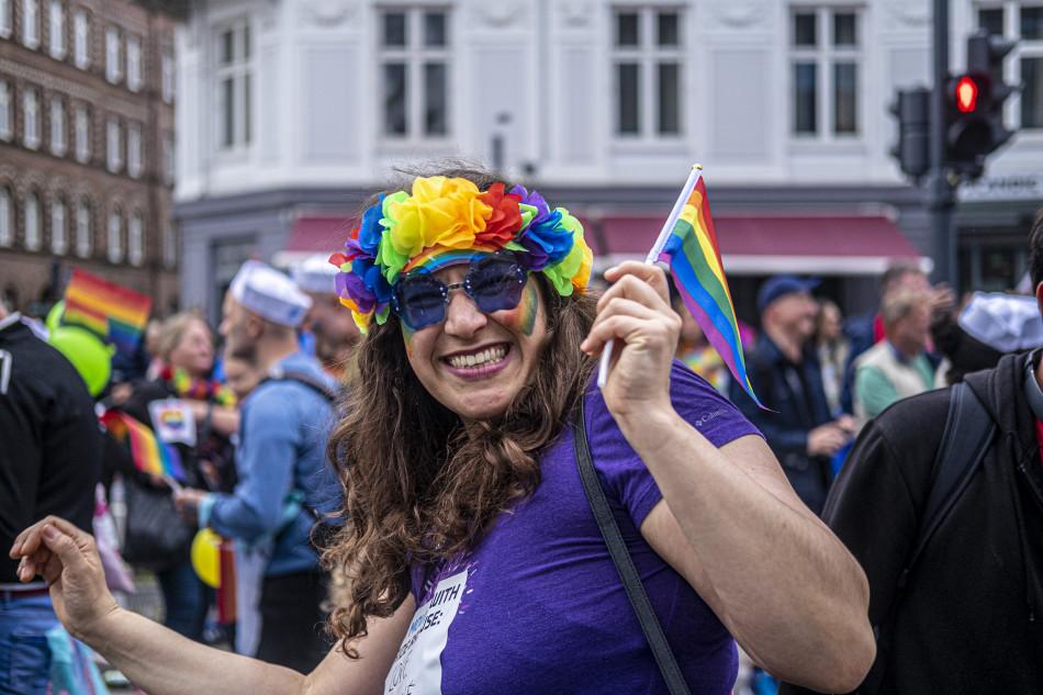 A DFDS employee waving at the camera during the Copenhagen Pride Parade 2019