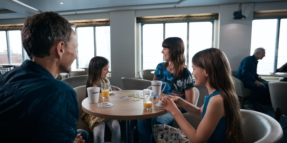 Family of four having a great time in Lighhouse Cafe onboard Eastern Channel Ferry.