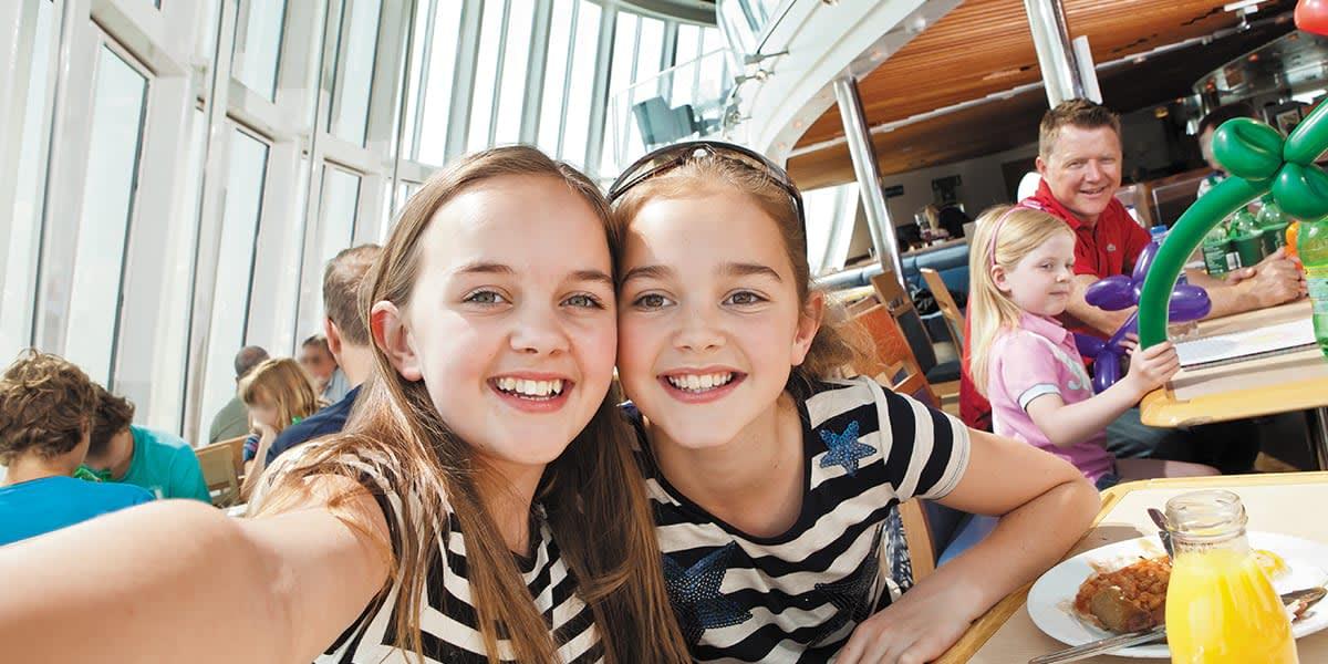 Zwei Mädchen sitzen am Tisch und machen selfie