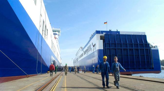 DFDS dock workers walking between two towering DFDS vessels