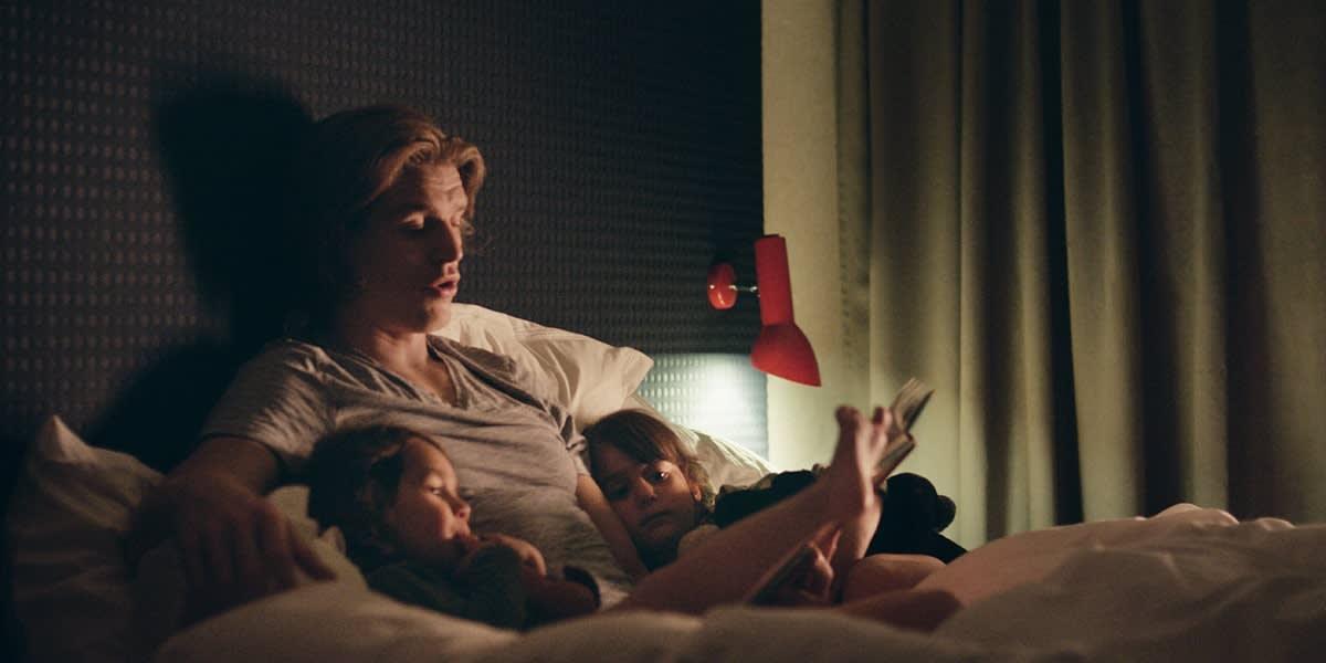 Far leser for barna på senga