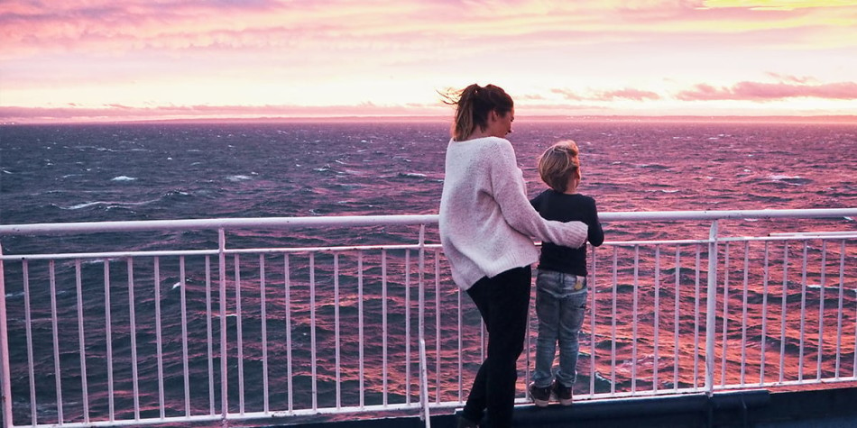 Mother and son on deck onboard DFDS ferry watching the sunset.