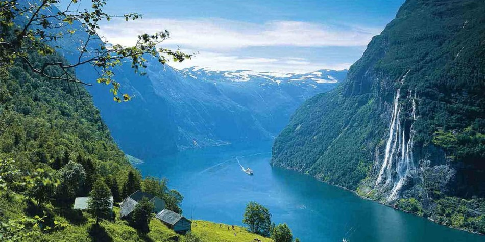 Fjord on a sunny day in Norway. A waterfall in running down into it and a boat is on the water.