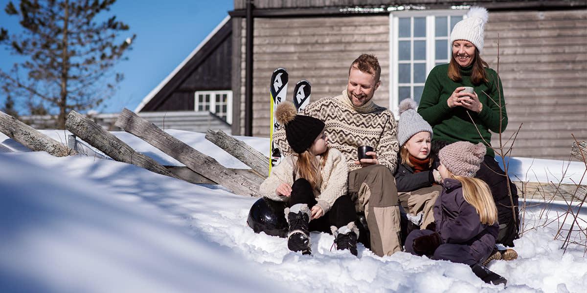 Familietid i sneen foran hytte i Norge - vinter