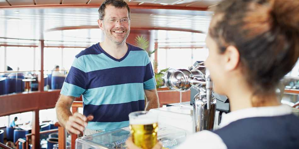 Man ordering a beer on the bar onboard DFDS Newhaven- Dieppe Transmache ferry.