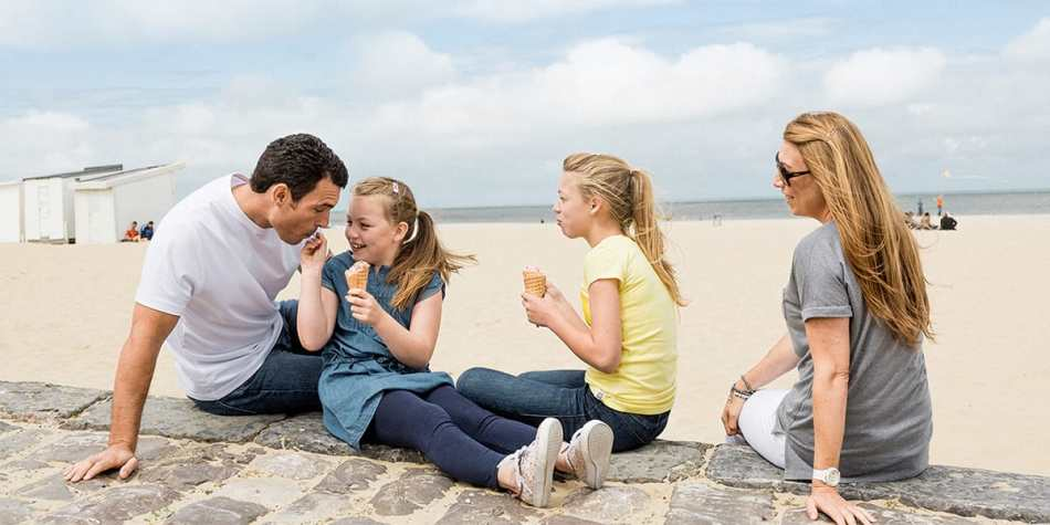 A family eating ice cream together on the beach