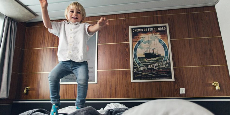 Child jumping on bed in commodore deluxe cabin