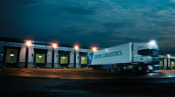 A DFDS logistics truck leaving a DFDS warehouse
