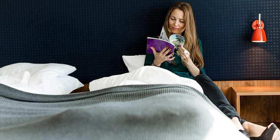 Woman reading a magazine on a double bed in a commodore de luxe cabin.