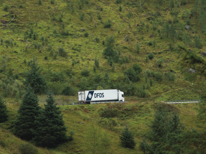 A DFDS truck drives in front of a mountain