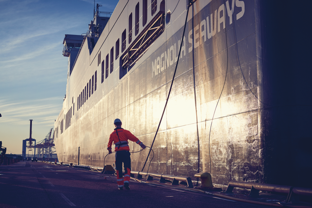 A DFDS Freight employee ensuring Magnolia Seaways is properly secured during an early-morning docking