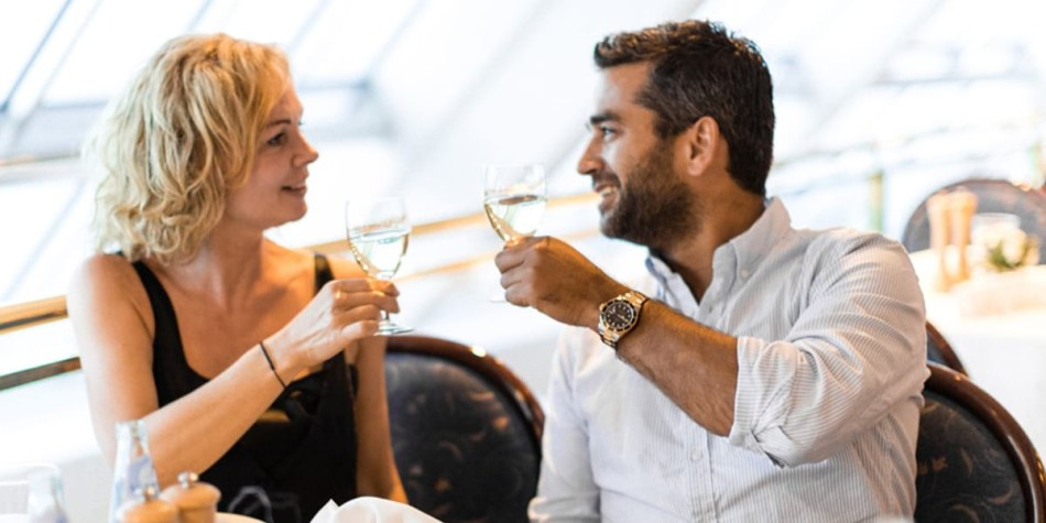 A couple making a toast with their glass of wine.