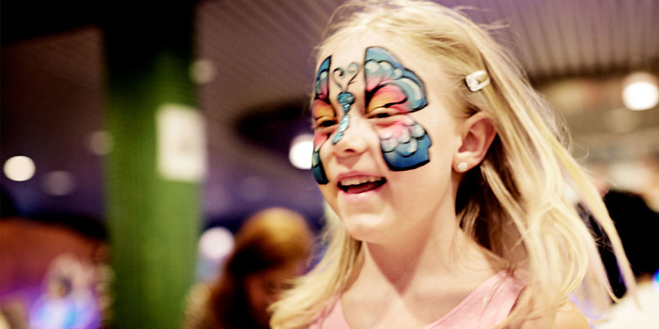 A little girl running around with face paint on.