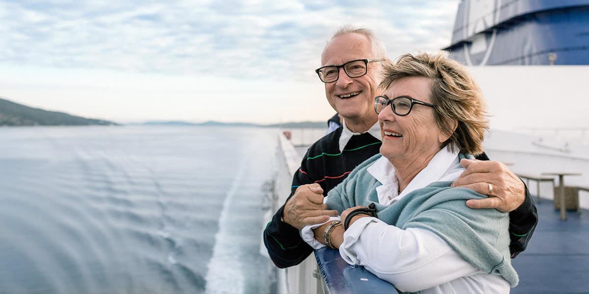 Ældre par på dæk som ser ud over havet