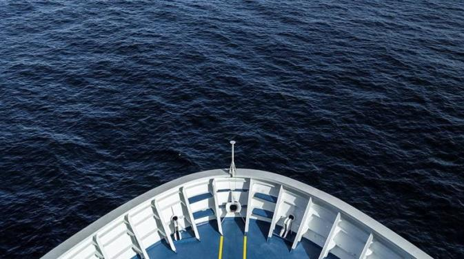Downward view of the ocean and the bow of a DFDS vessel