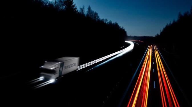Long exposure image of a DFDS truck on a road at night