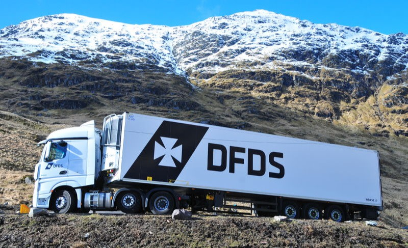A white DFDS lorry driving through mountains