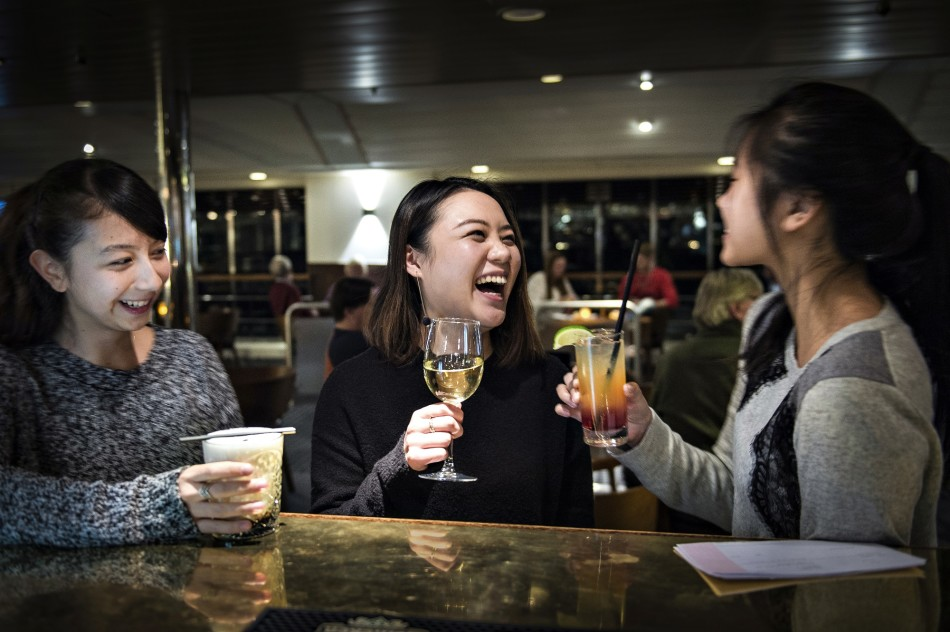 Asian tourists enjoying drinks in the Compass Lounge aboard a DFDS vessel