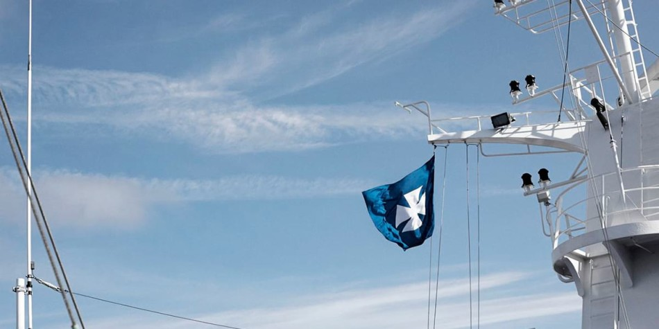 A DFDS flag blowing in the wind on one of the ships