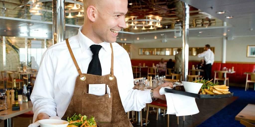 Servitør bringer rettene til bordet i Explorers Steakhouse