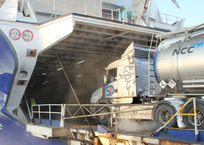 A truck and trailer marked with hazardous cargo boarding a DFDS vessel