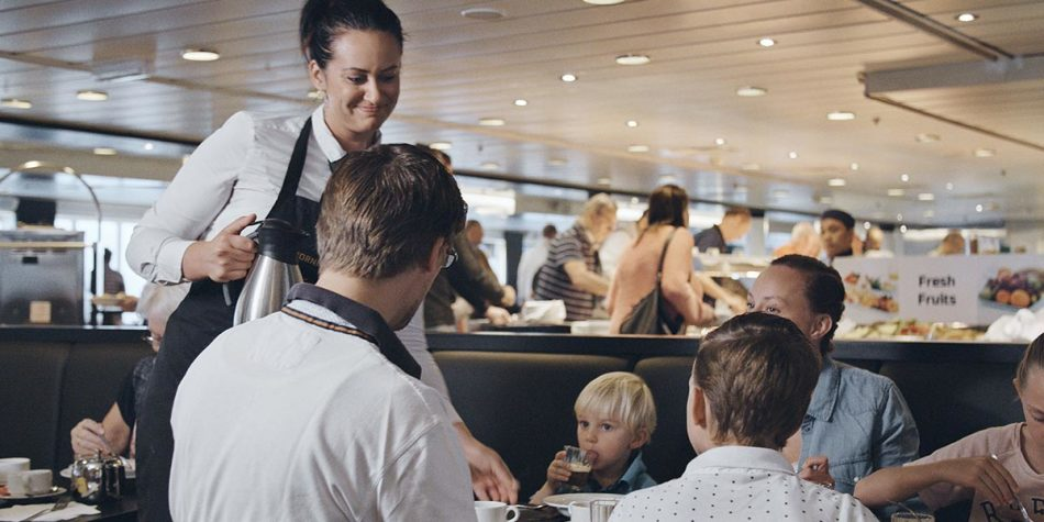 Waitress serving family dining onboard