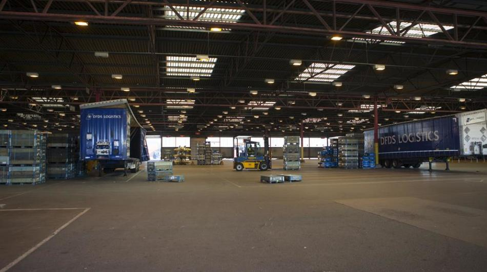 A forklift loading cargo onto two DFDS Logistics trucks inside a DFDS warehouse