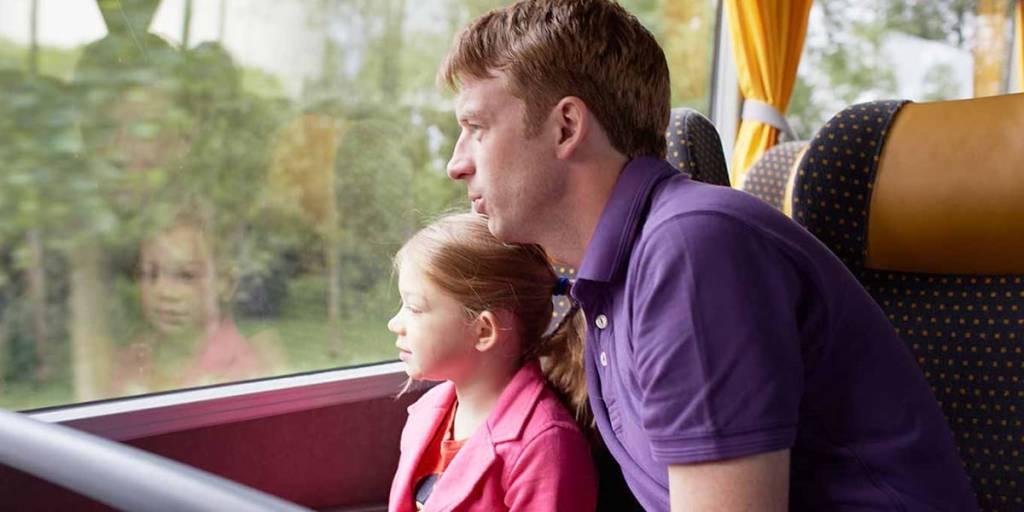 Far og datter ser ut av bussvinduet