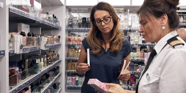 Kobieta wybiera perfumy w sklepie duty-free