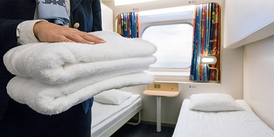 A person holding two, folded, white towels out in front of two single beds in a sea view cabin.
