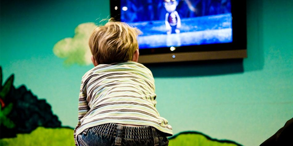 A little boy watching a cartoon television program in the kids club.
