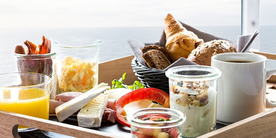 A selection of breakfast options (such as yogurt, croissants, bacon) on a tray.
