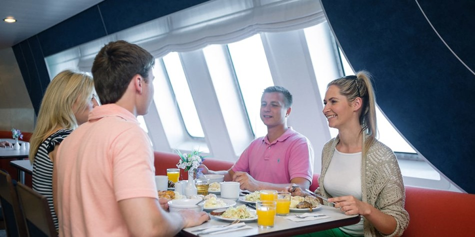 A group of people enjoying a meal at restaurant onboard Athena Seaways in the Baltics.