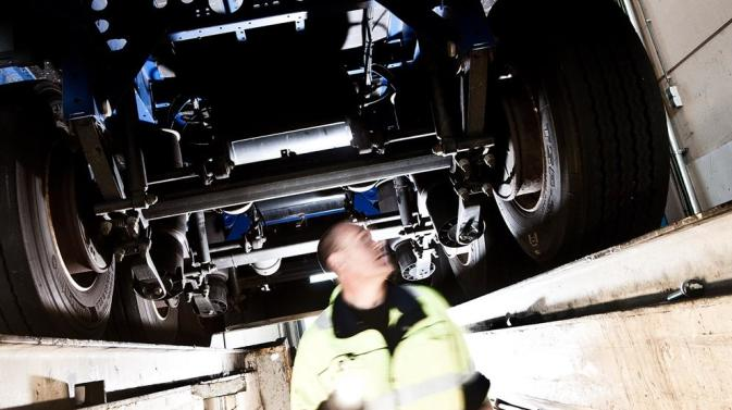 DFDS employee inspecting a truck's undercarriage
