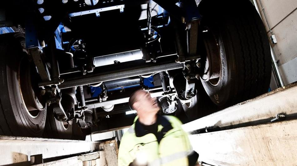 A DFDS employee inspecting a truck's undercarriage
