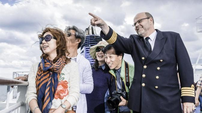 DFDS captain pointing out the sight to Asian tourists
