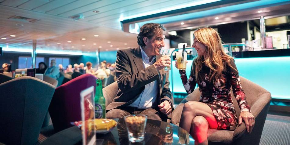 Couple enjoying a drink in Columbus Club onboard Newcastle-Amsterdam
