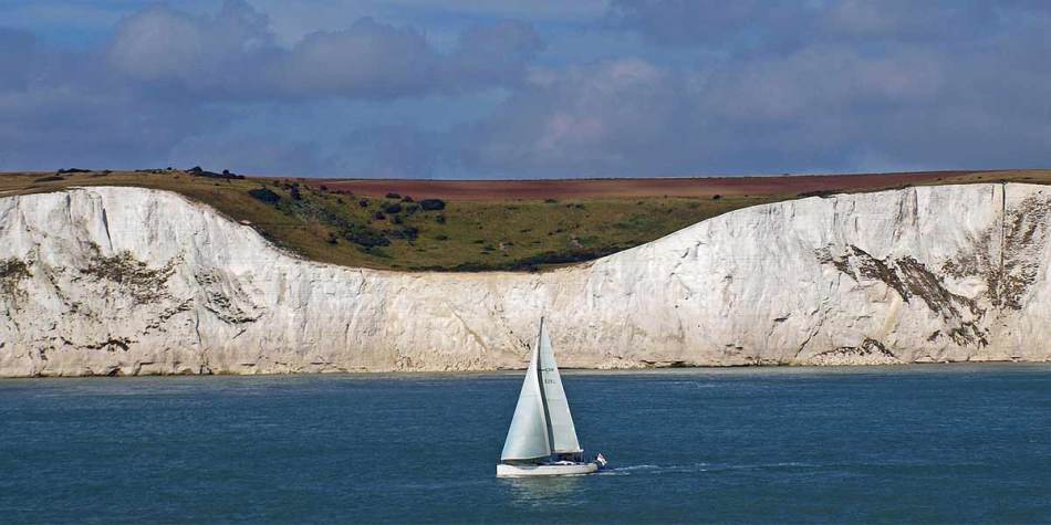 White cliffs of Dover and a sailing boat in the water