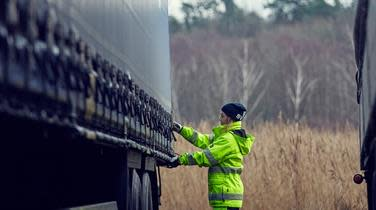 DFDS Logistics employee securing tie-downs on a truck